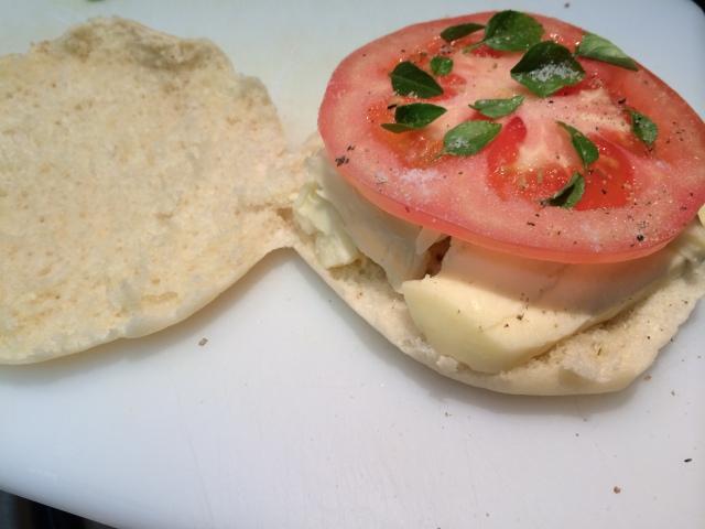 Montagem do sanduíche: abre o pão sírio, coloca as fatias de queijo embaixo, a fatia de tomate em cima e algum folhinhs de manjericão cobrindo. Fecha o sanduíche.