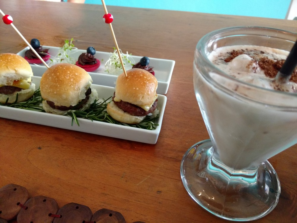 Mini Cheese Burger de Fraldinha com Cebola Caramelizada e Emmental; Milk Shake de Ovomaltine; Mini Macarron de Frutas Vermelhas com Ganache de Chocolate